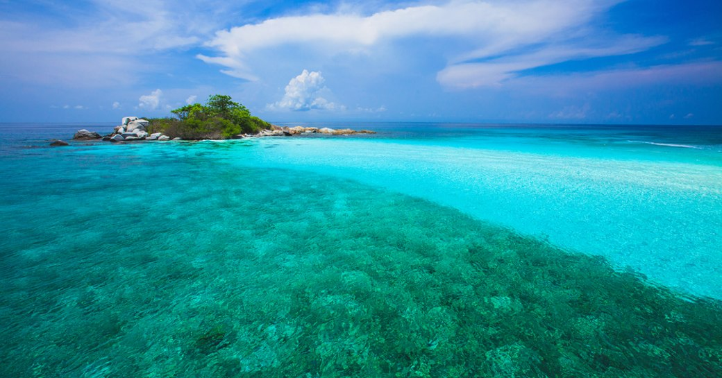 A shallow turquoise sea with blue sky above at Racha Yai island in Thailand