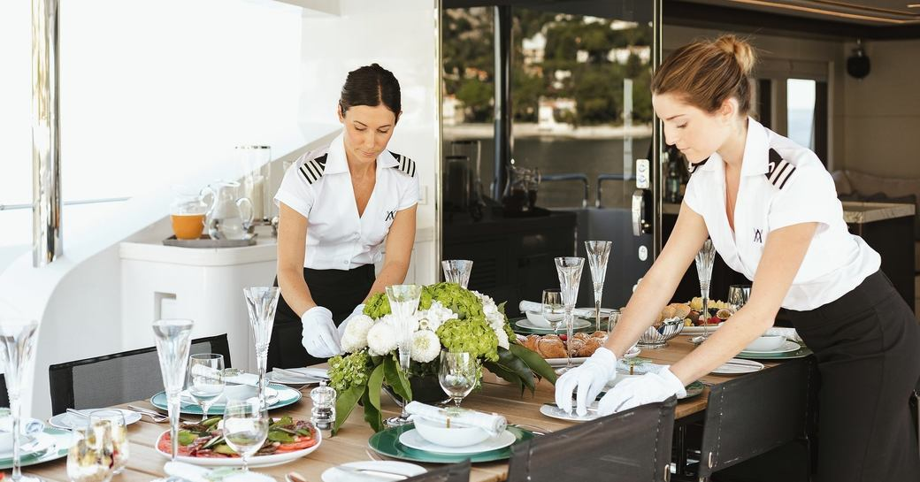 yacht crew fix table on superyacht before dining