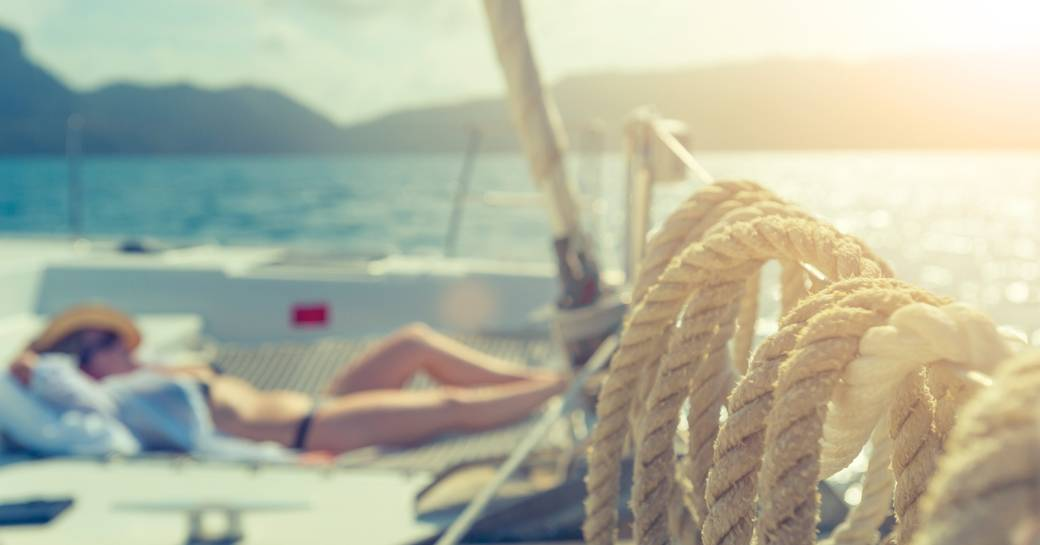 charter guests relaxes on deck of a sailing yacht while cruising in the Whitsundays