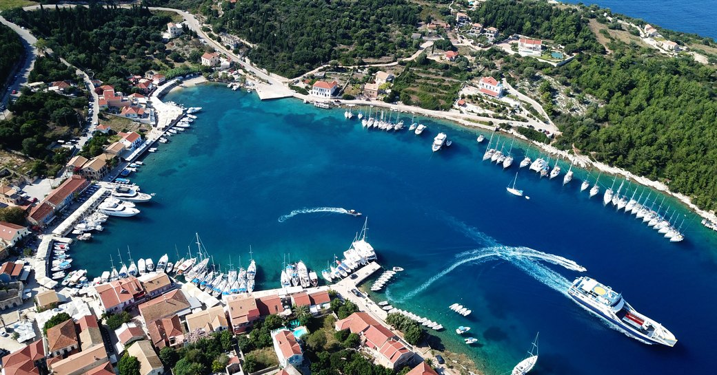 luxury harbour in greece with aerial view of yachts leaving port