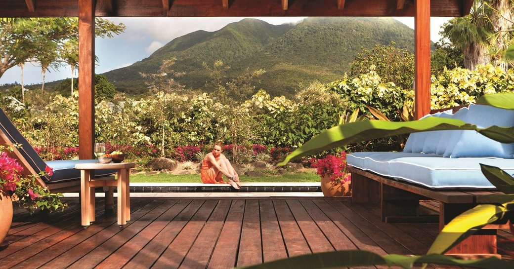 A spa guest sitting by a swimming pool in Nevis