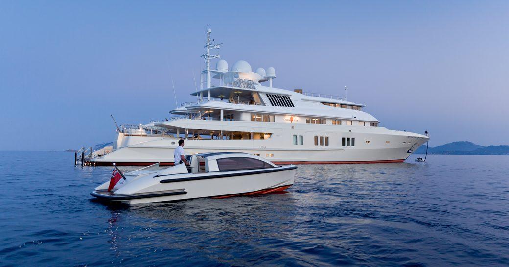 luxury yacht Coral Ocean cruising alongside tender on a luxury yacht charter in Antigua