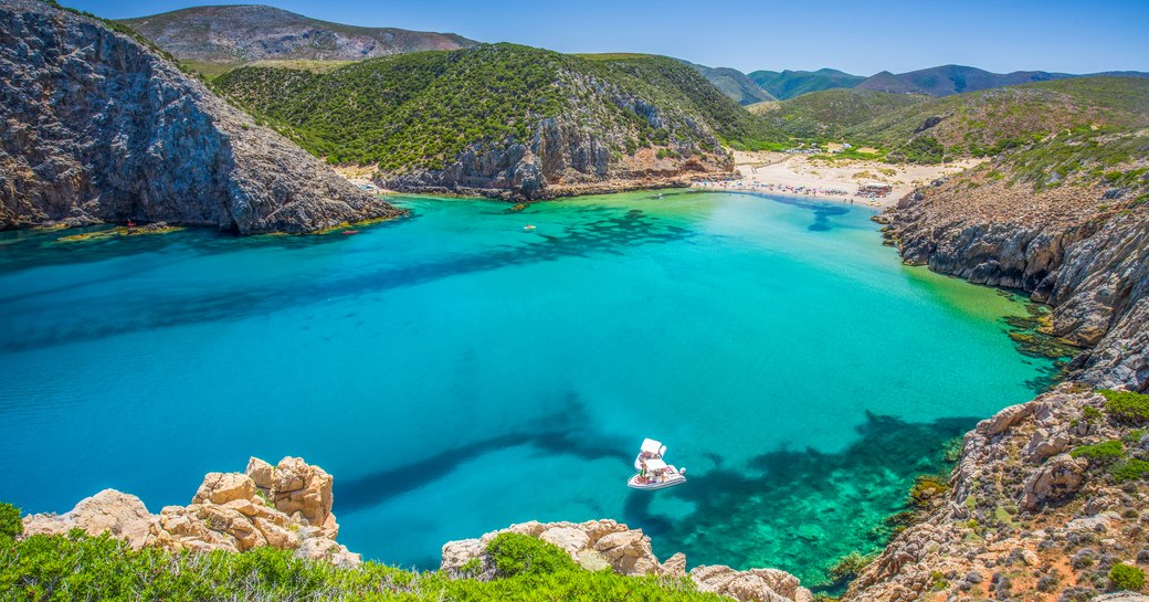 Bright blue water in secluded bay in Sardinia, with Mediterranean terrain surrounding