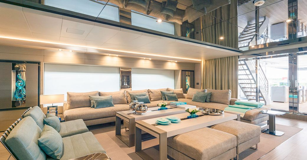 main salon on luxury superyacht utopia iv, with blue and gray furniture