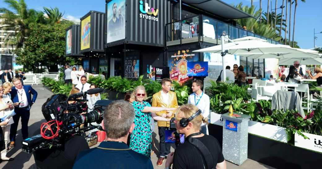 Exterior view of ITV stand at MIPCOM, camera crew and presenters working outside.