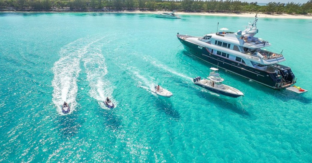 superyacht in the clear blue sea of the bahamas with tenders alongside