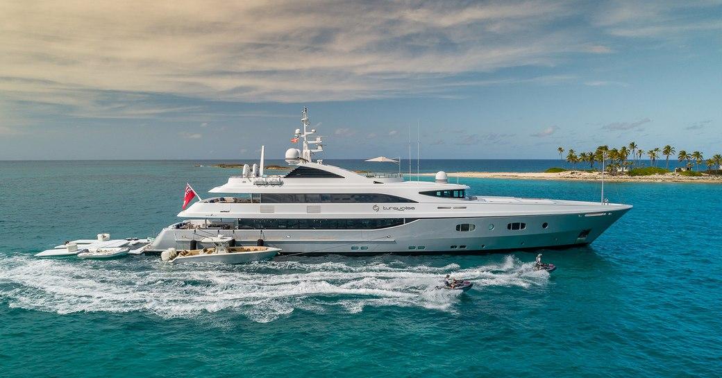 yacht in the open sea, with tenders alongside