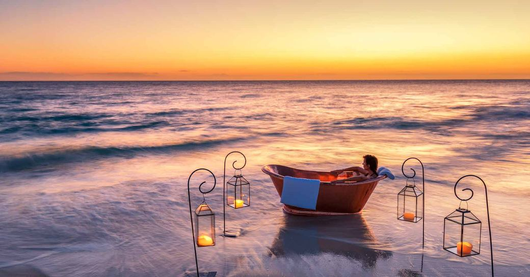 woman relaxes in copper bath on the beach surrounded by lanterns on thanda island