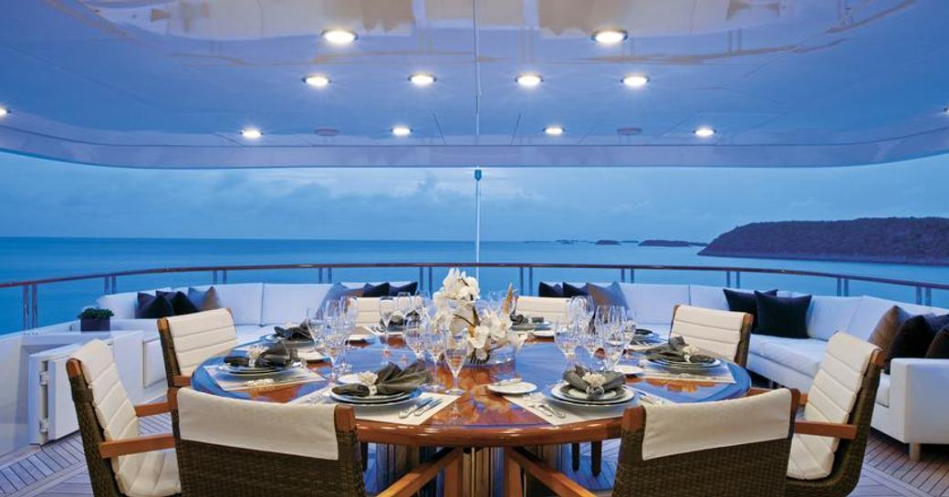 alfresco dining table on luxury charter yacht alessandra at sunset, with views of the ocean in the bahamas in background