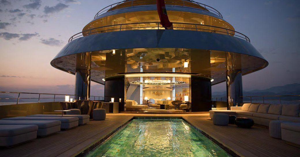 relaxing by the swimming pool while watching sun set behind the luxury superyacht Savannah