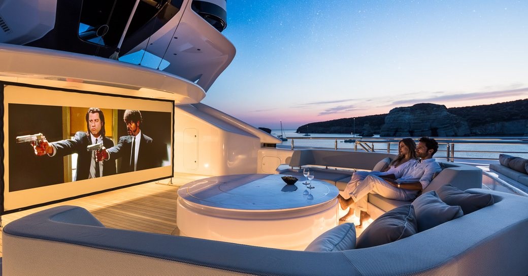 Couple sitting on deck of superyacht O'PARI watching film on large screen