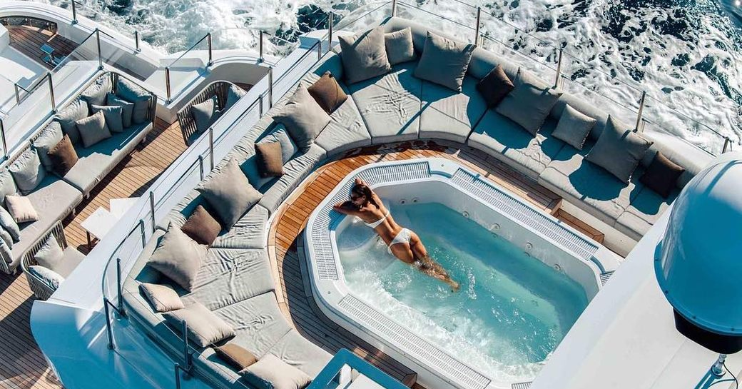 Charter guest relaxes in aft deck swimming pool on board luxury yacht