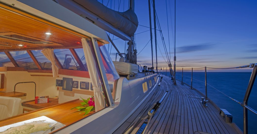 view of sunset from side deck of superyacht JUPITER with view into main salon