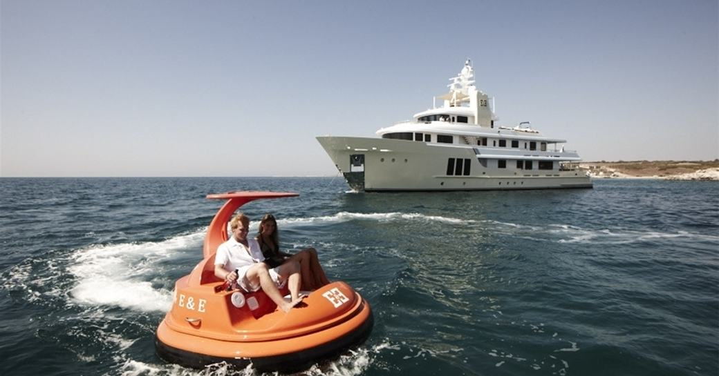 luxury yacht E&E anchors on charter while guests play on water toys