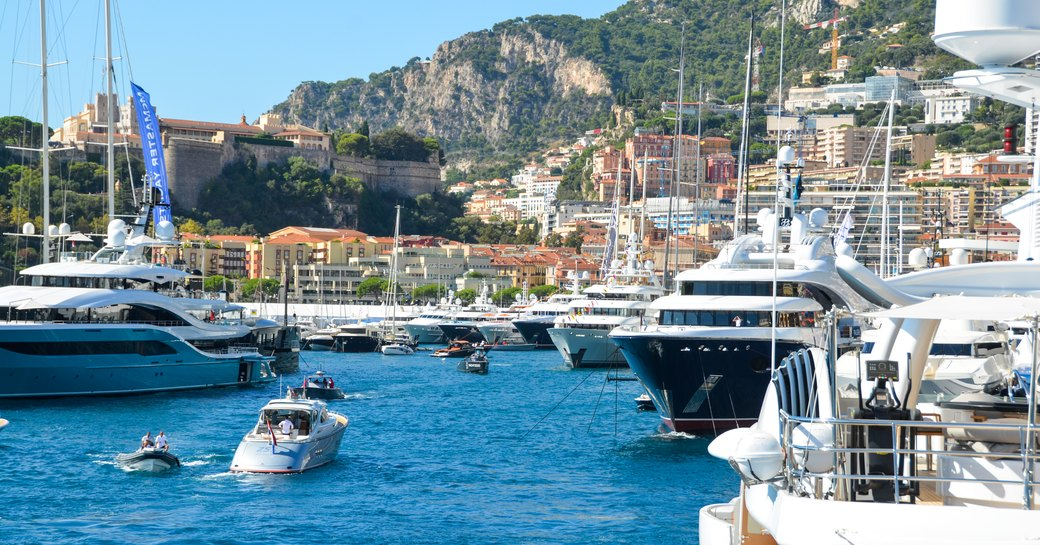 busy port hercules in monaco on a bright summers day, superyachts docked across the harbour
