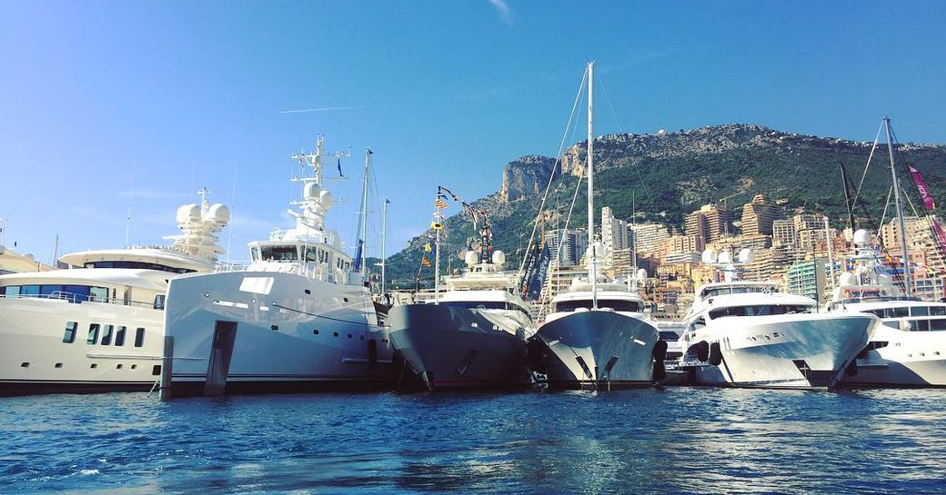 The bows of six luxury yachts lined up in Port Hercules for the Monaco Yacht Show 2017