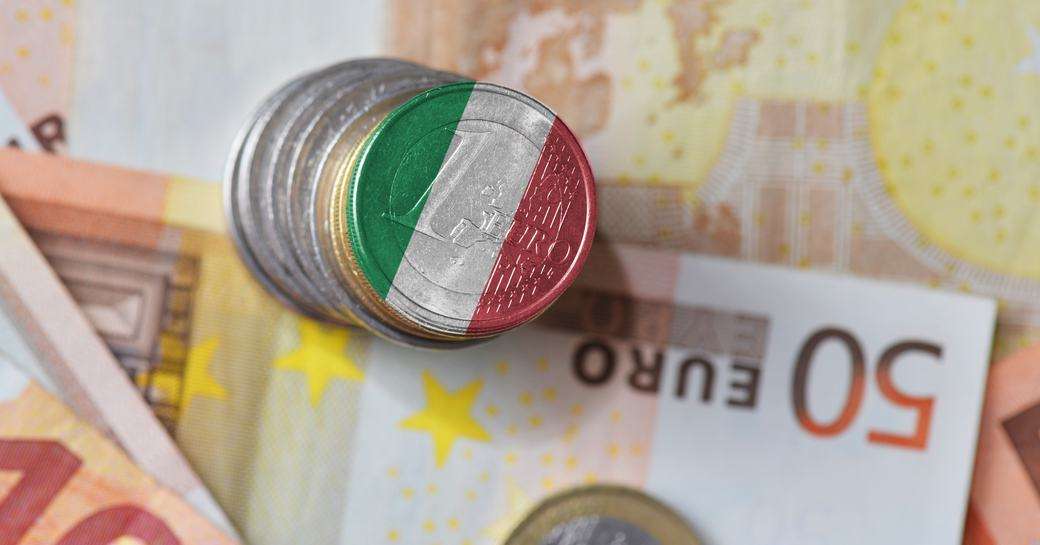 Coins on euro note with Italian flag printed