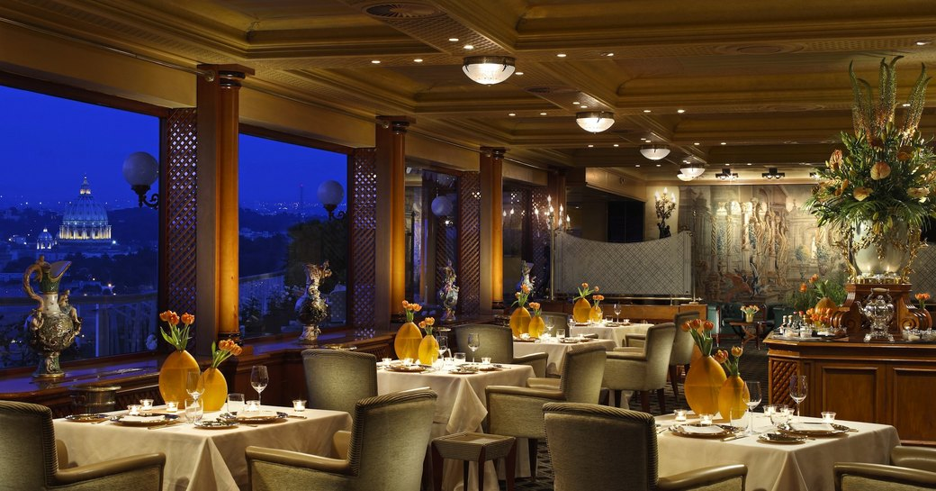 Grand interiors of La Pergola restaurant in Rome, with great views and stunning flower vases