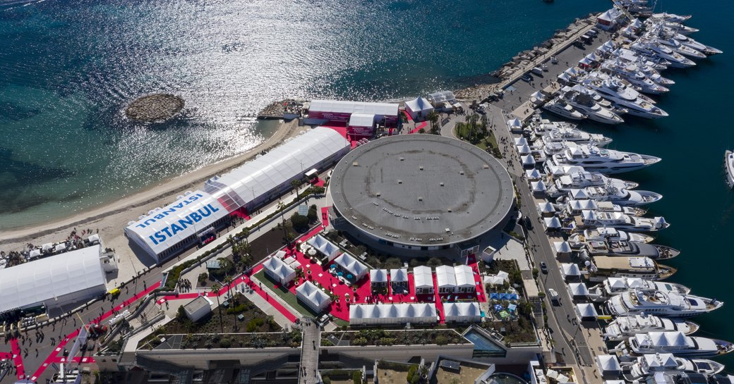 Aerial overview of MIPIM Cannes, many motoryachts moored in marina adjacent to exhibition building and tents.