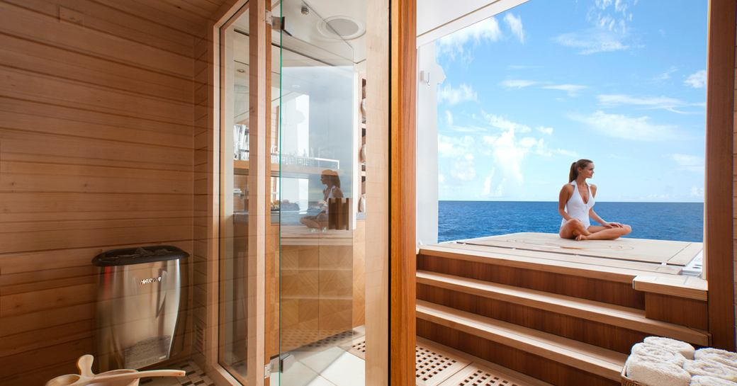 A charter guest sits cross-legged on a foldout balcony attached to a superyacht