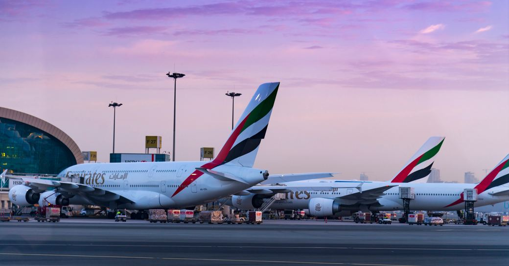 planes lined up on the runway at Abu Dhabi International Airport as dusk falls