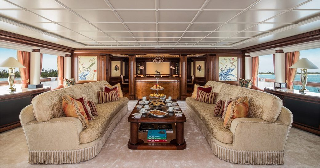 two sofas facing each other with cream tea setup on the coffee table in the main salon aboard luxury yacht CALYPSO