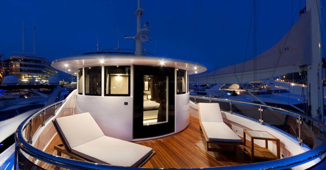 Superyacht GATSBY owners private balcony at night with sunloungers on deck