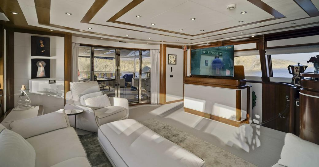 salon area on board superyacht bunker, with white sofas and exterior set-up