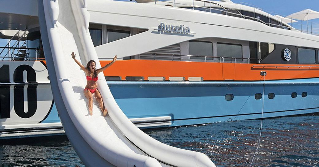 Woman going down water slide on a yacht