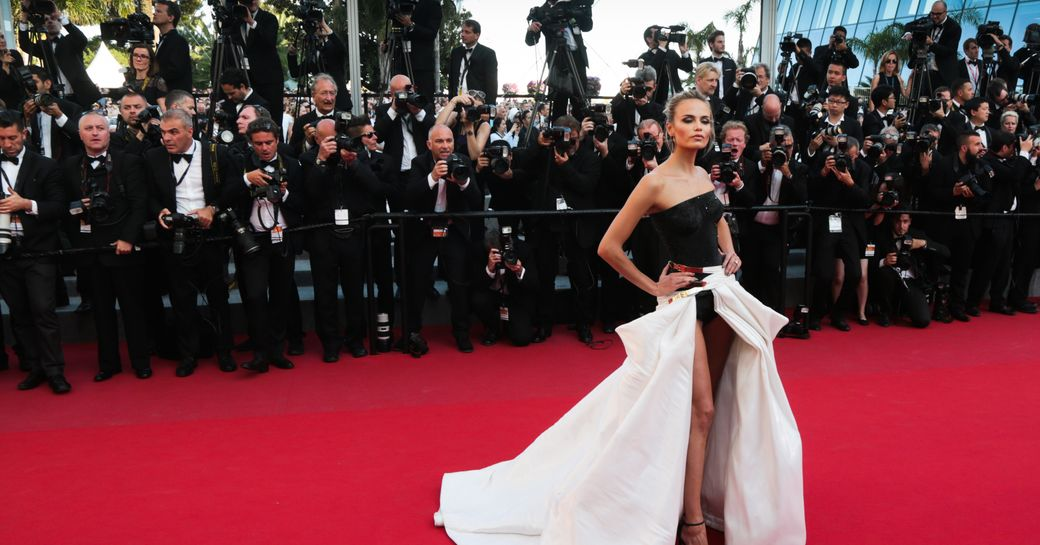 Supermodel poses on red carpet at Cannes Film Festival, with photographers behind her taking pictures