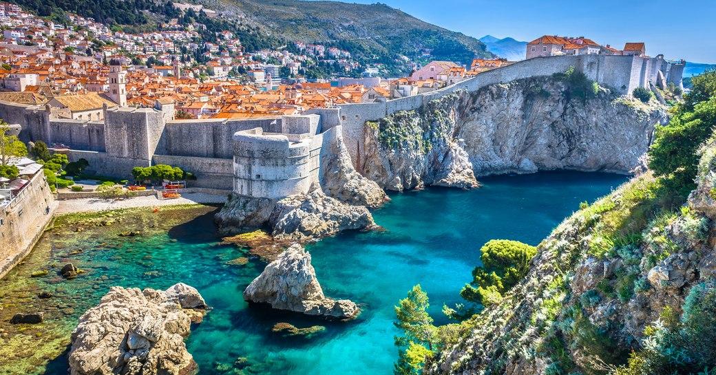 coastline in croatia, with old buildings and bright blue sea