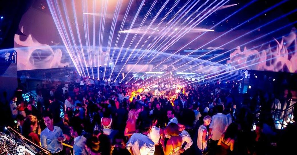 People dancing in busy space at MAD nightclub on Yas Island with strobe lights reaching out to the ceiling