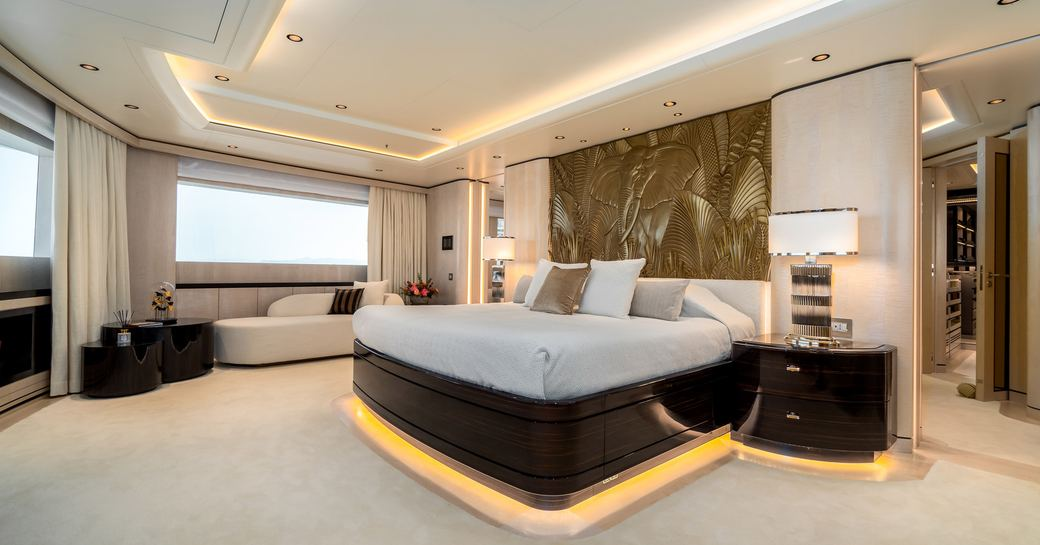 Large lightly colored suite on superyacht O'PARI, with king sized bed with artwork behind