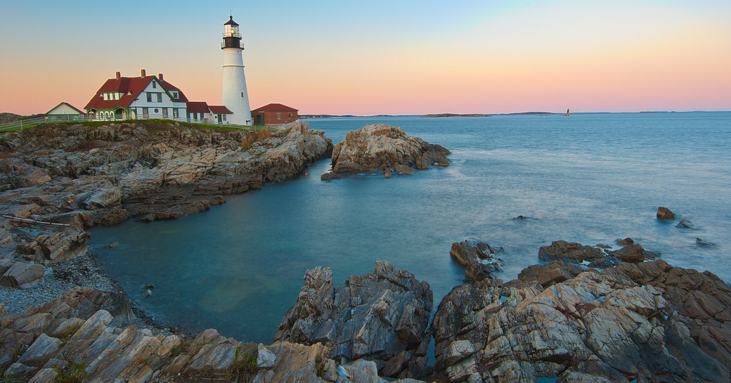 lighthouse on the coast of new england a popular luxury yacht charter vacation destination