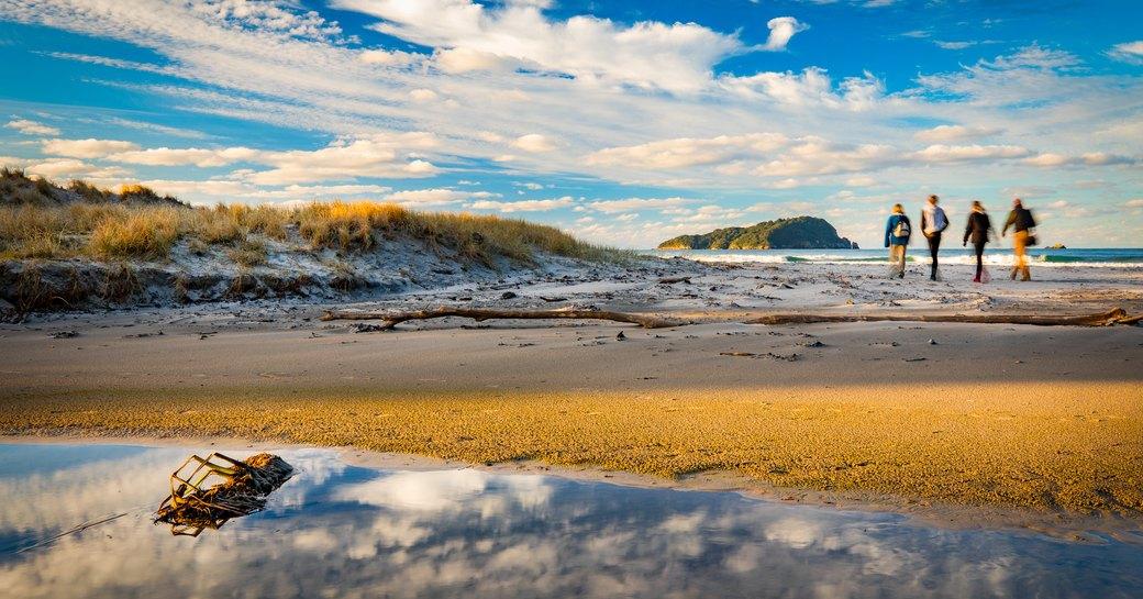 four travellers walk along Pauanui Beach, Coromandel Peninsula, New Zealand