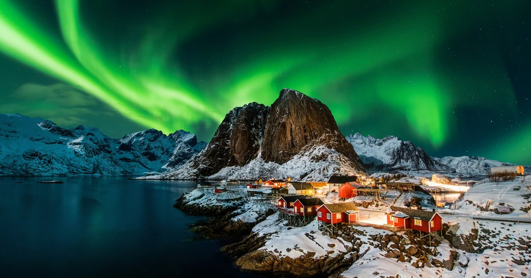 northern lights above town next to the water in norway