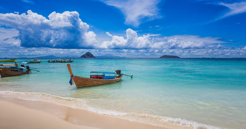 Beach at Laem Tong beach, Ko Phi Phi, showing wooden rowing boat in shallow water, blue sky above