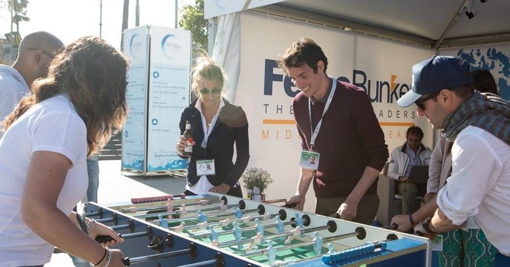 Exhibitors and visitors partaking in a table football match at MYBA event in Barcelona.