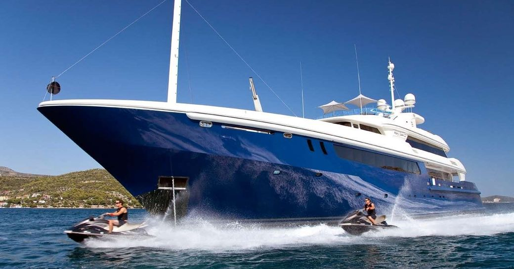 luxury yacht Mary-Jean II anchors on a Caribbean yacht charter while jet skis take to the waters