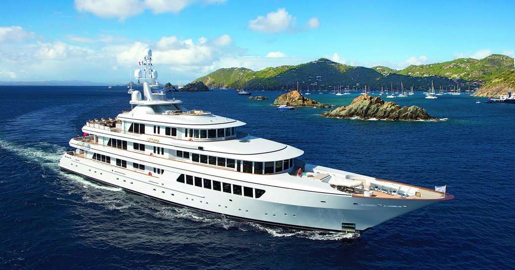 Profile shot of superyacht UTOPIA on the water with Caribbean islands in the background