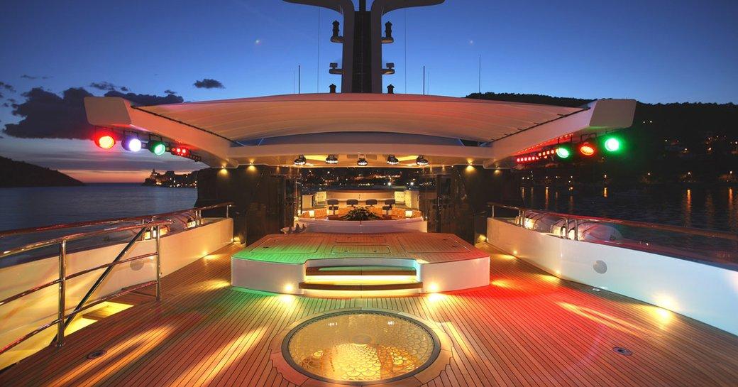 night shot of benetti superyacht st david's sun deck, with coloured lights creating dancefloor and private nightclub