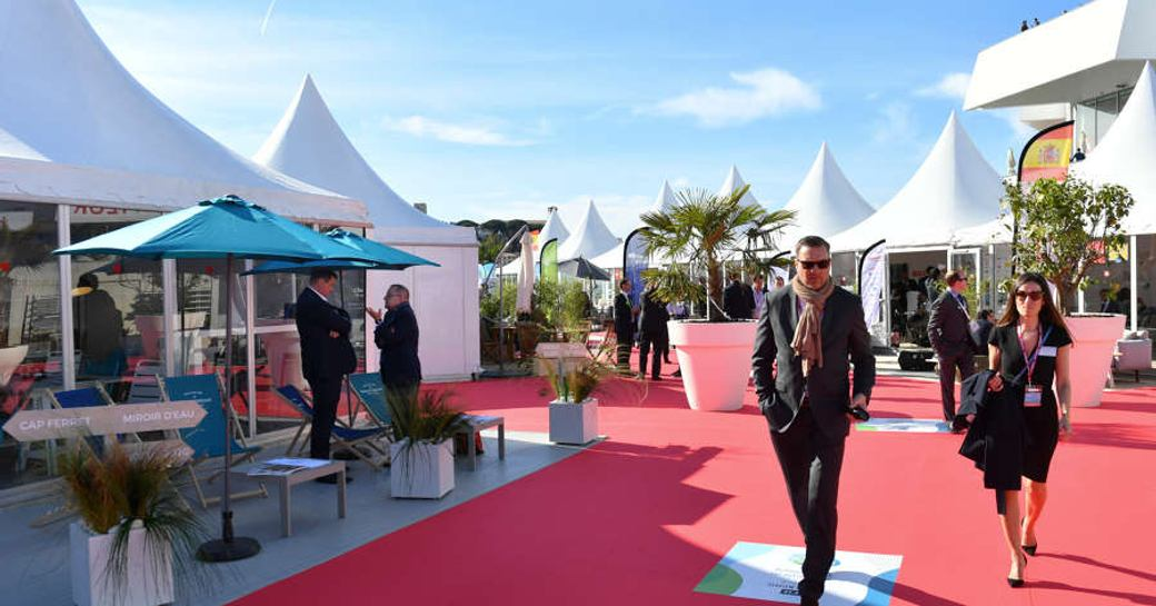 Exhibitors tents, red carpet and visitors walking through at MIPIM event.