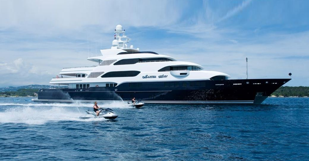 superyacht Martha Ann anchors on a yacht charter as jet skis take to the water