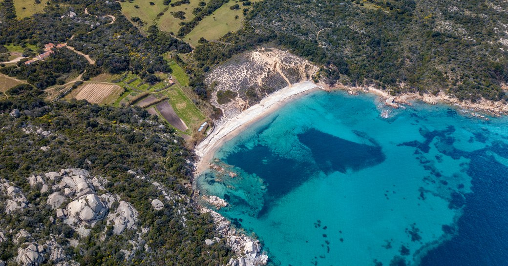 Bright blue lagoon surrounding small bay in Sardinia