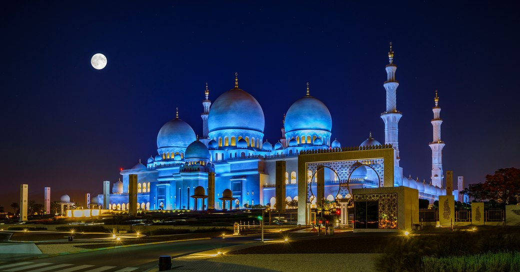Sheikh Zayed Grand Mosque in Abu Dhabi lights up at night with a full moon in the sky above