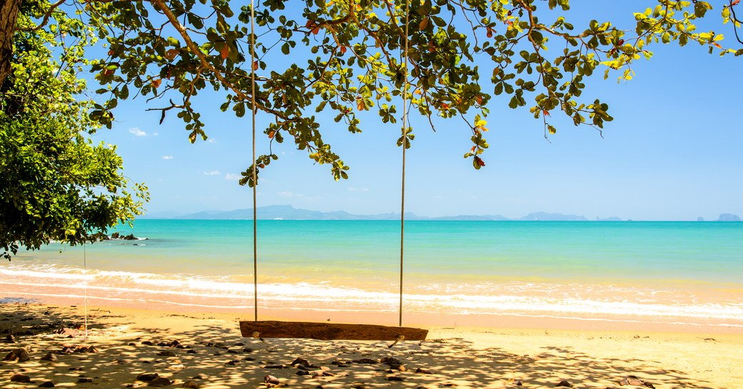 Wooden swing with turqoise sea in Thailand
