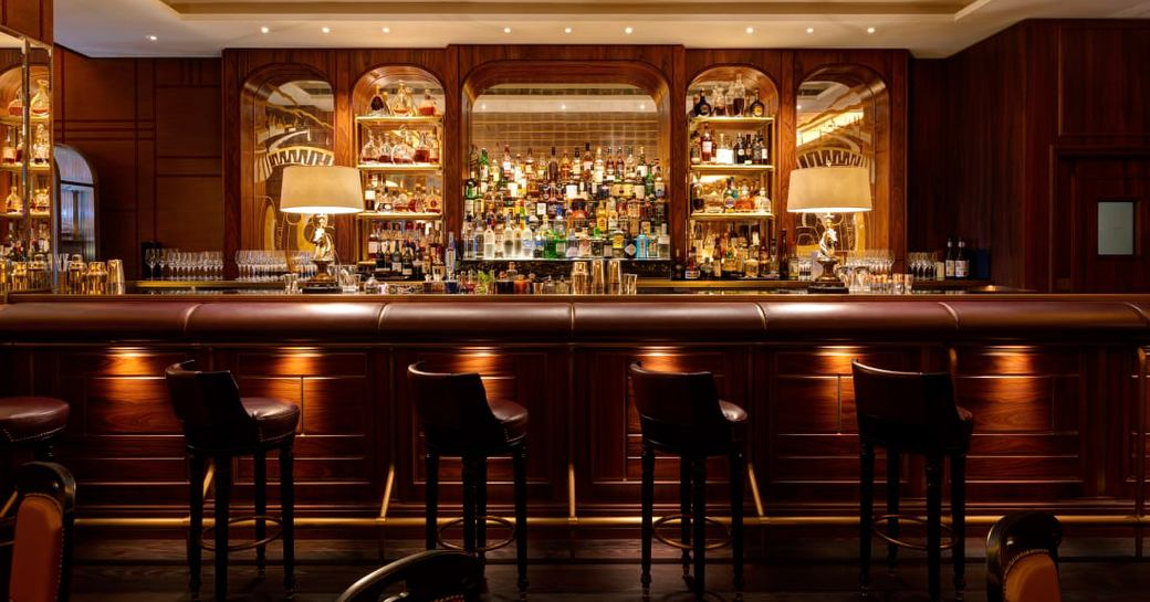 bar of le bar americain in monaco, with leather bar stools and bottles behind the bar