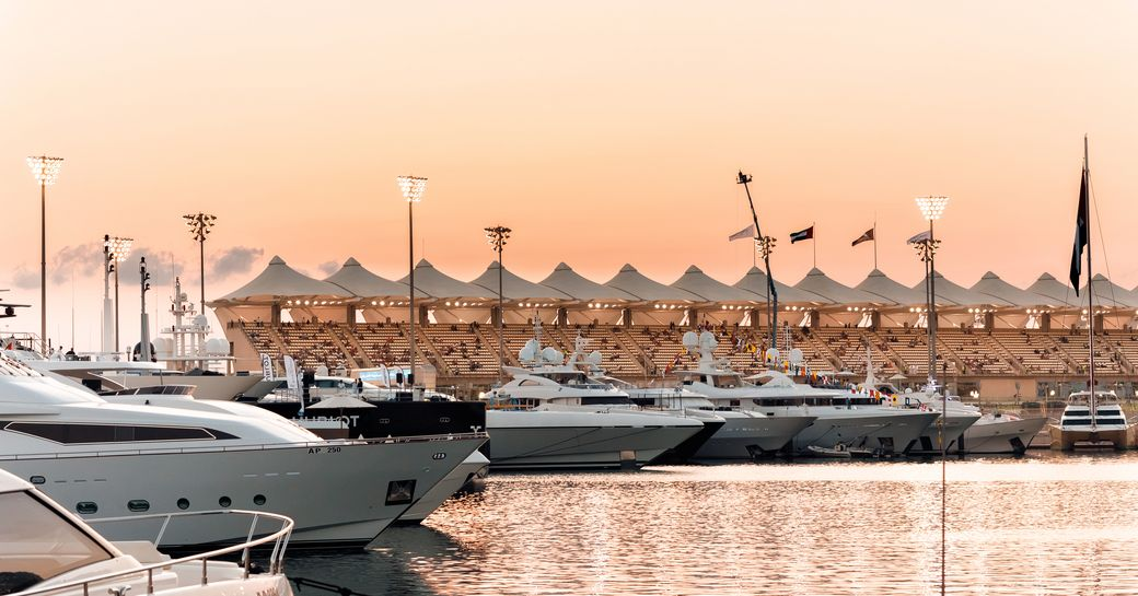 Superyachts in Yas Marina at sunset, with views over the water and grandstands in the background