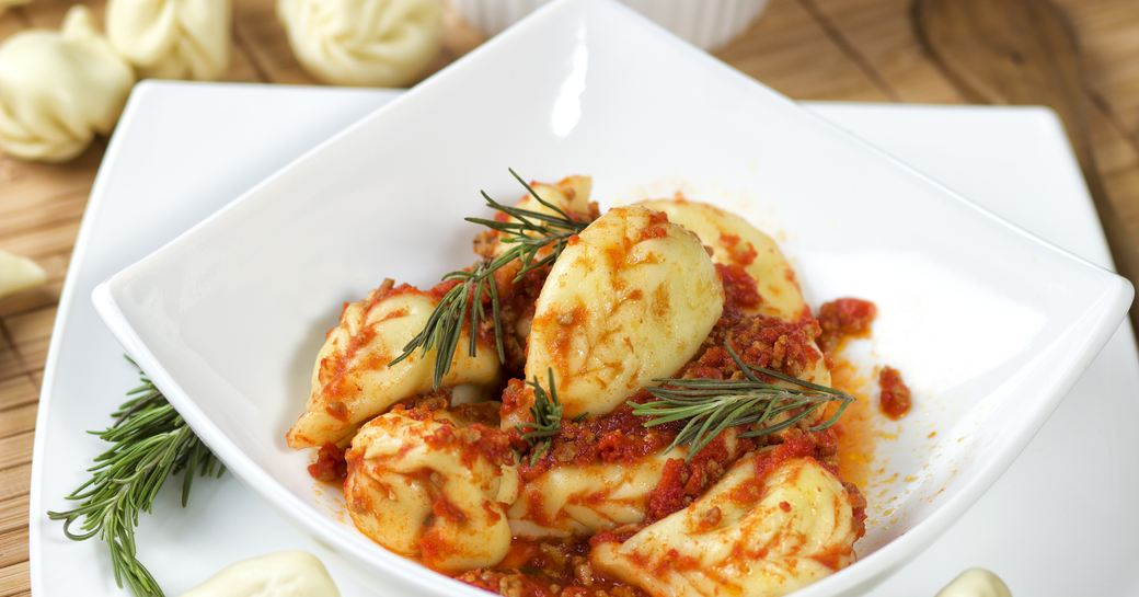 A white bowl of culurgiones, a traditional Sardinian pasta dish, with tomato sauce and rosmary sprigs
