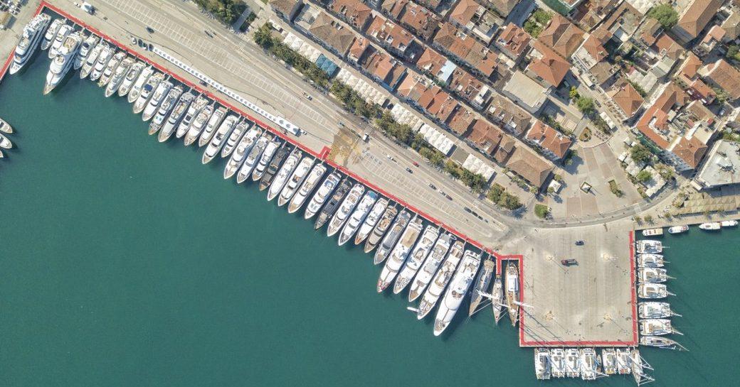 Aerial bird's eye view of Mediterranean Yacht Show, multiple moto yachts moored along docks.